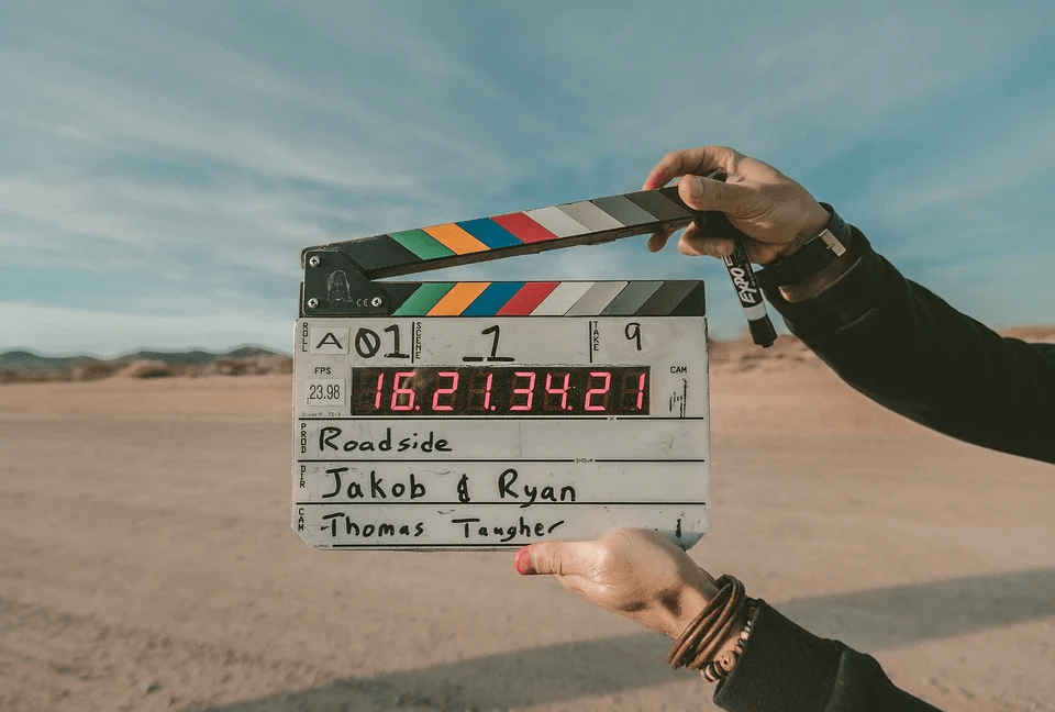 blue sky, deserted land, a person holding a clapperboard